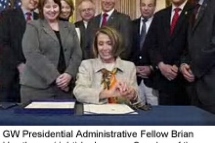 group of men and women in suits, including Brian Hawthorne, look on as Nancy Pelosi signs bill