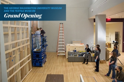 Museum staff members install the 14-foot rug to the gallery walls.