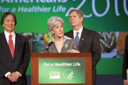Kathleen Sebelius speaks at a For a Healthier America podium with Howard Koh, om Vilsack and Robert C. Post behind her