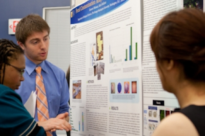 student presenting research board at symposium