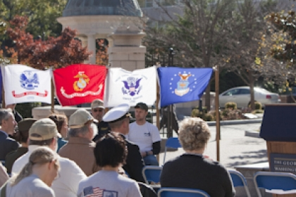 Steven Knapp speaks at podium in Kogan Plaza on veterans day with military flags & members of the university community watching