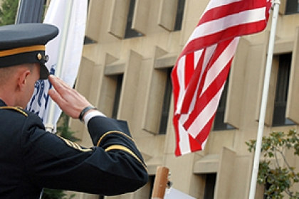 man in military uniform salutes American flag in Kogan Plaza