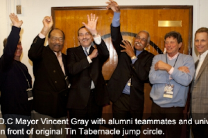 Vincent Gray with members of the university community raising arms in front of original Tin Tabernacle jump circle