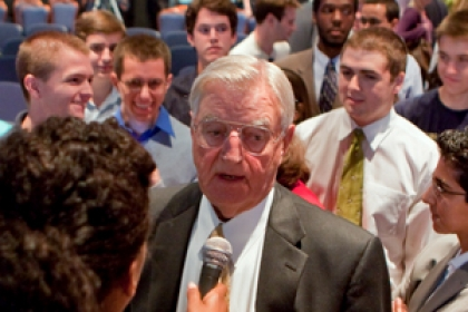 Walter Mondale speaks in to microphone while surrounded by students
