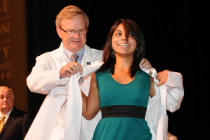 student receiving white coat on stage
