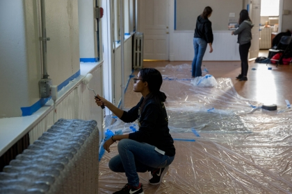 A volunteer helps paint walls at Douglas Memorial Church in Northeast Washington, D.C. (Photo: Logan Werlinger/GW Today)