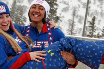 smiling Elana Meyers holds up bobsled teammate in Olympic uniform